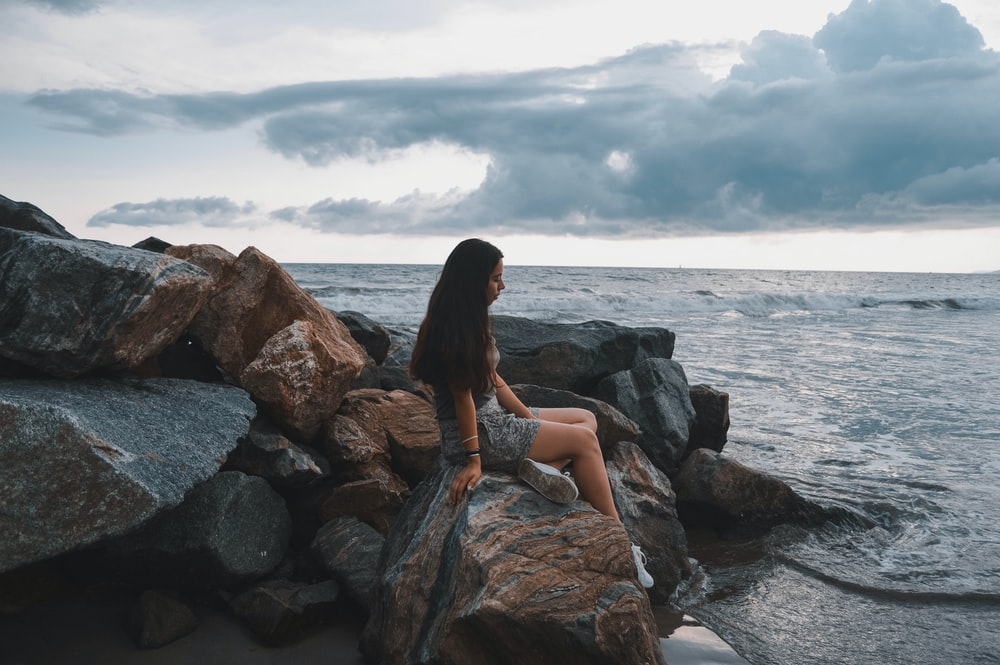 woman sitting on rocks by the seashore during daytime