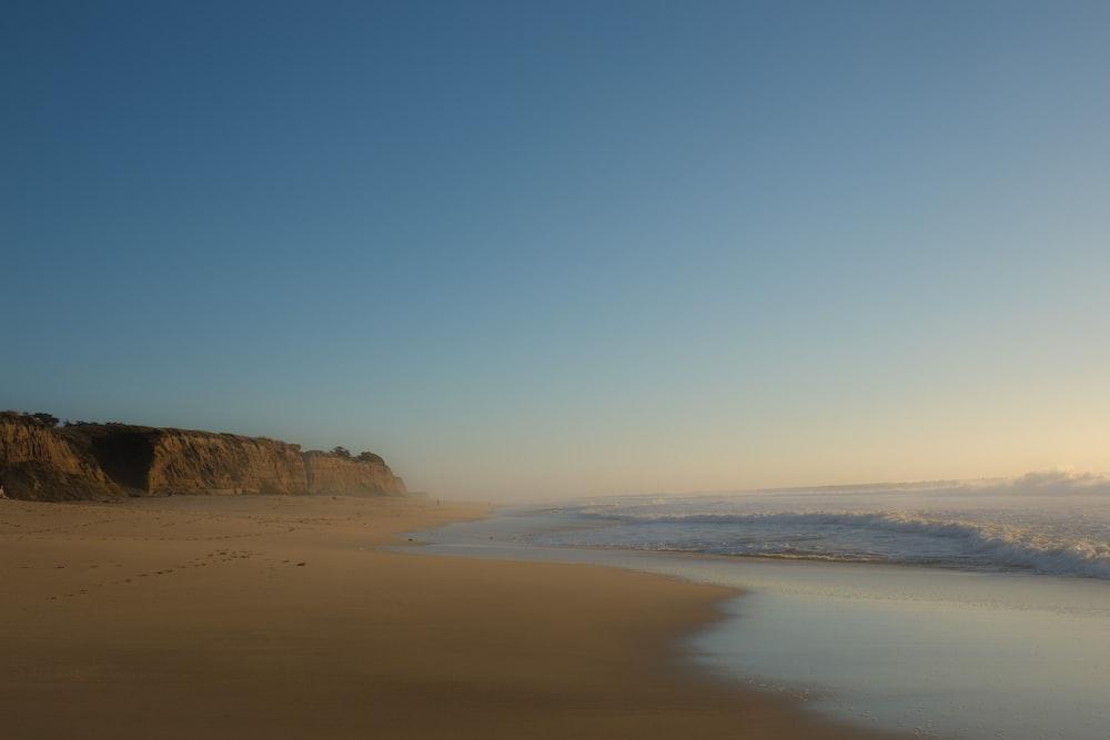 brown seashore under clear blue sky