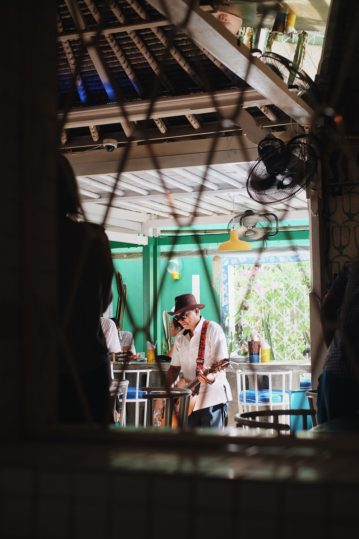 shallow focus photo of man wearing black hat playing guitar
