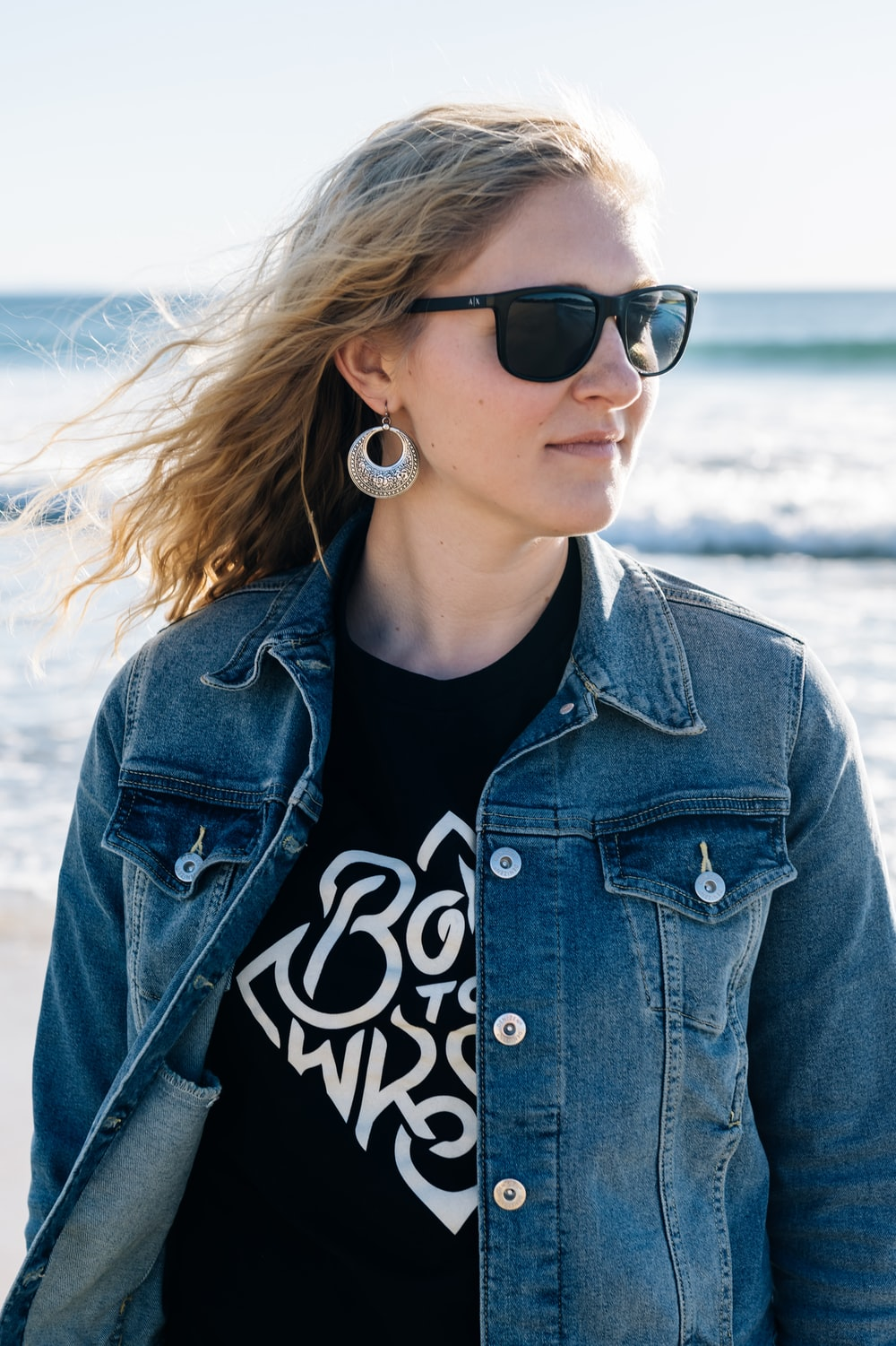 selective focus photography of woman wearing blue denim jacket standing on seashore