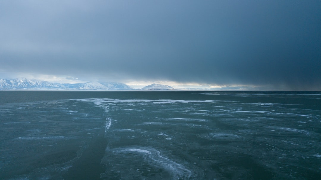 An Unremarkable Photo of Some Melting Ice With A Storm Coming With Some Mountains In the Distance. I Like To Call This One: Rage, Rage Against the Dying of the Light. - unsplash