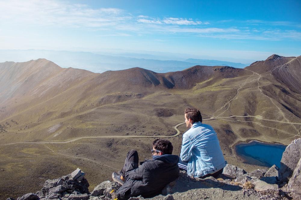 two men sitting on mountain during daytime