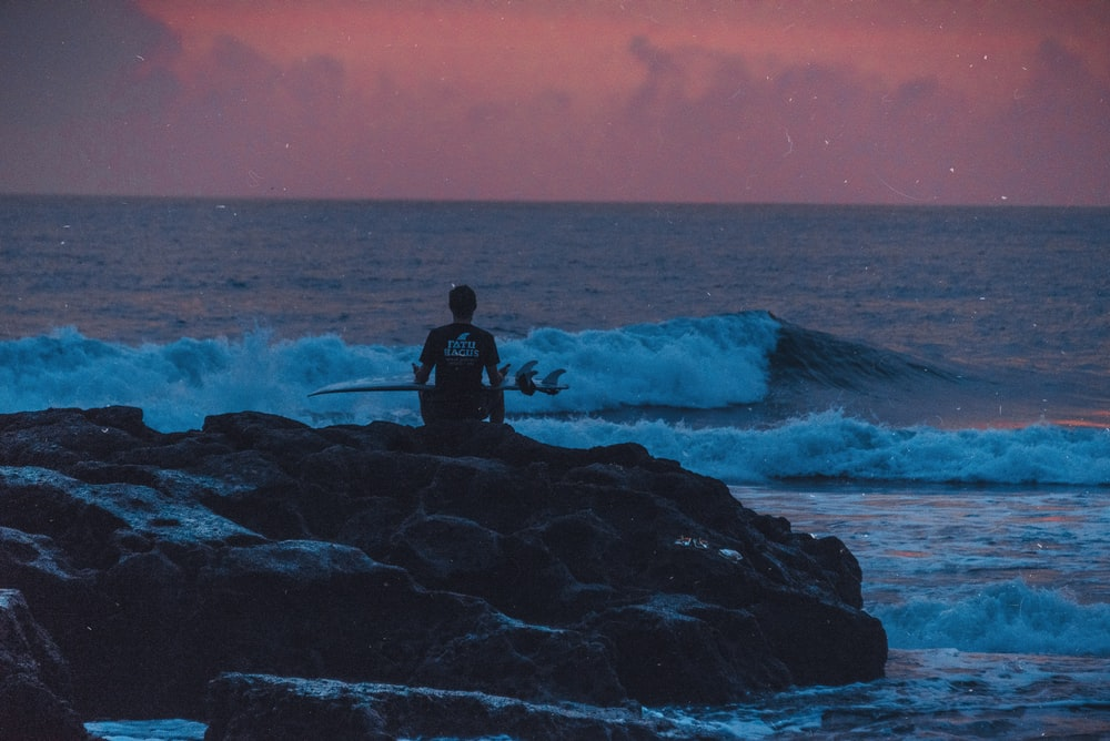 man holding surfboard while sitting on rock formation near body of water