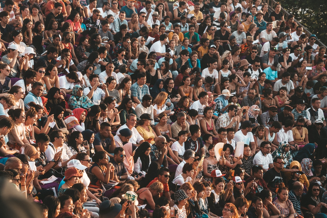 A large crowd of people sitting in raked seating.