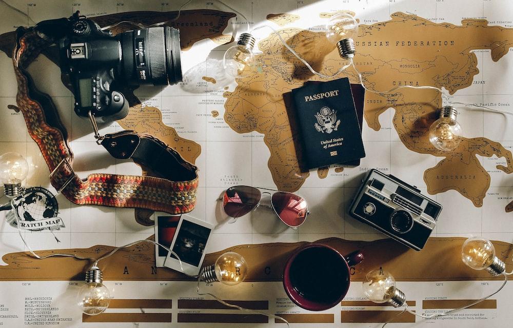 black DSLR camera near passport