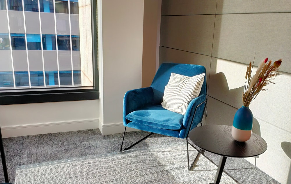 blue fabric sofa chair near brown wooden pedestal table