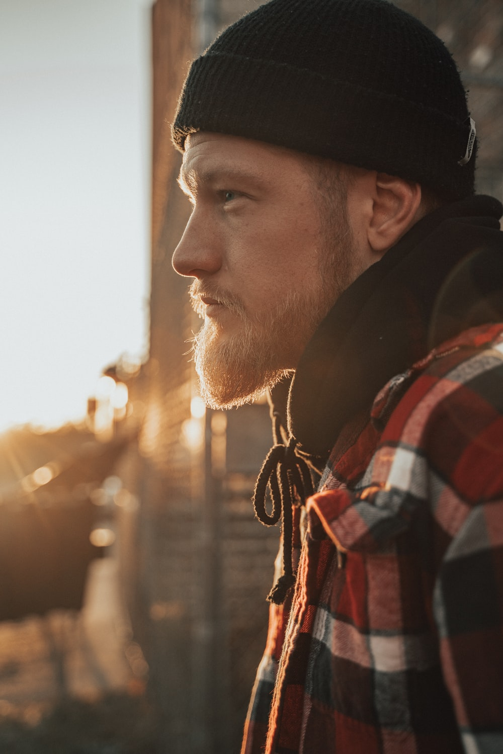 man in red, white, and black plaid jacket and beanie cap