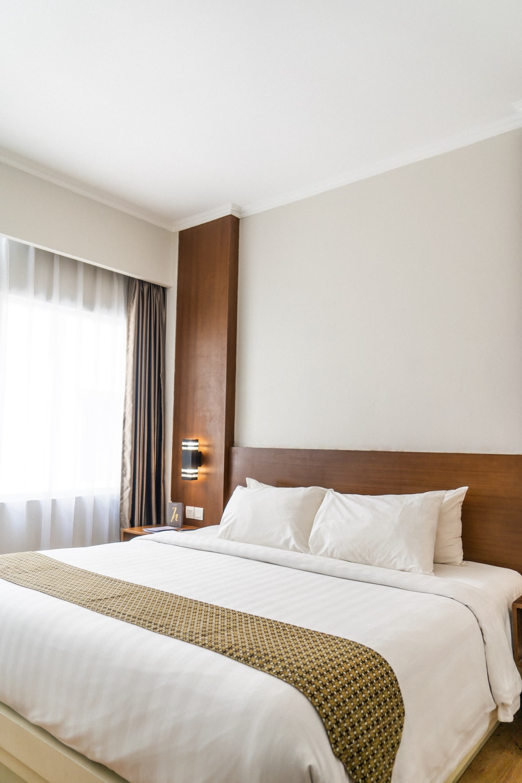black sconce beside white bed