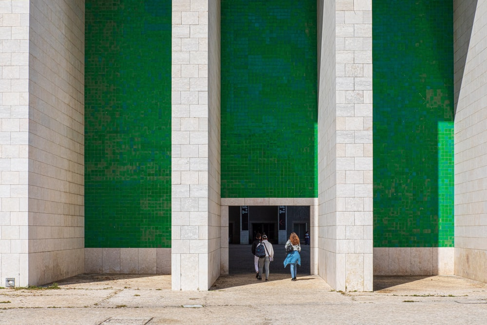 man and woman walking towards green and white building