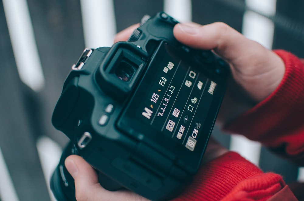 black and gray DSLR camera turned-on