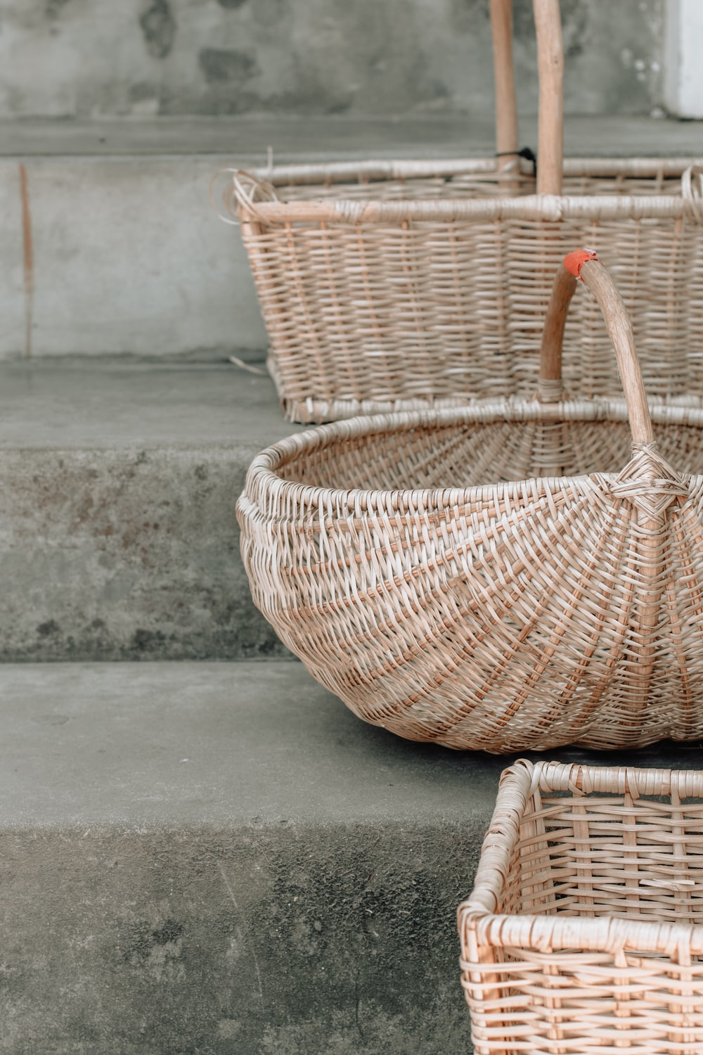 three brown wicker baskets on stairs