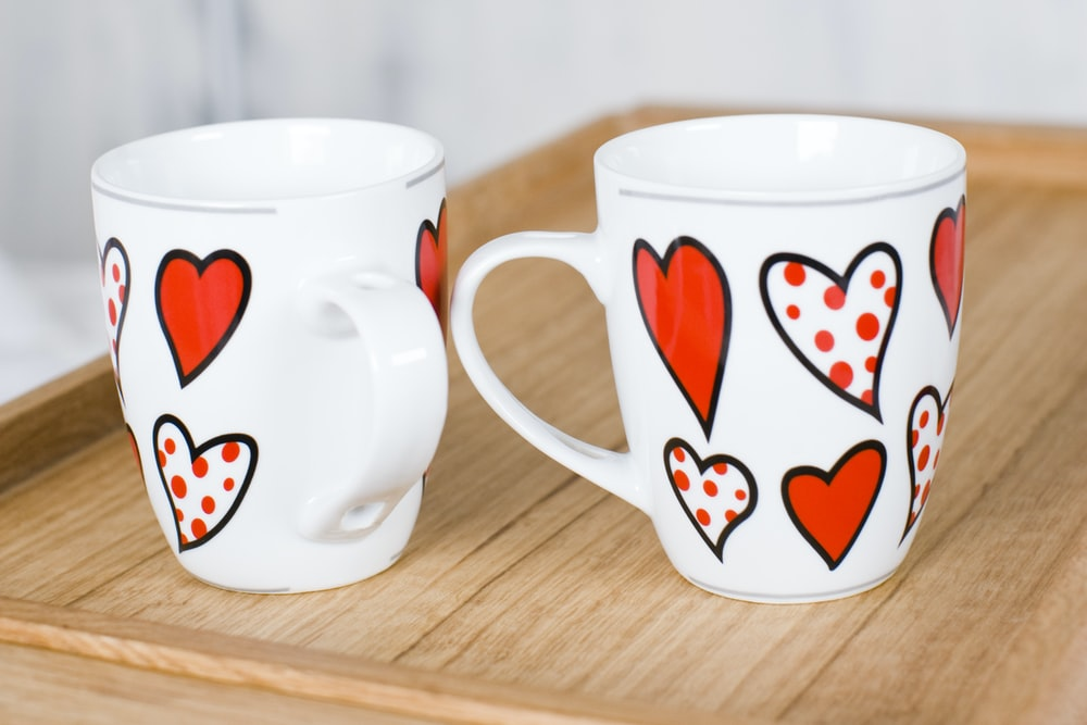two white-and-red heart print ceramic mugs