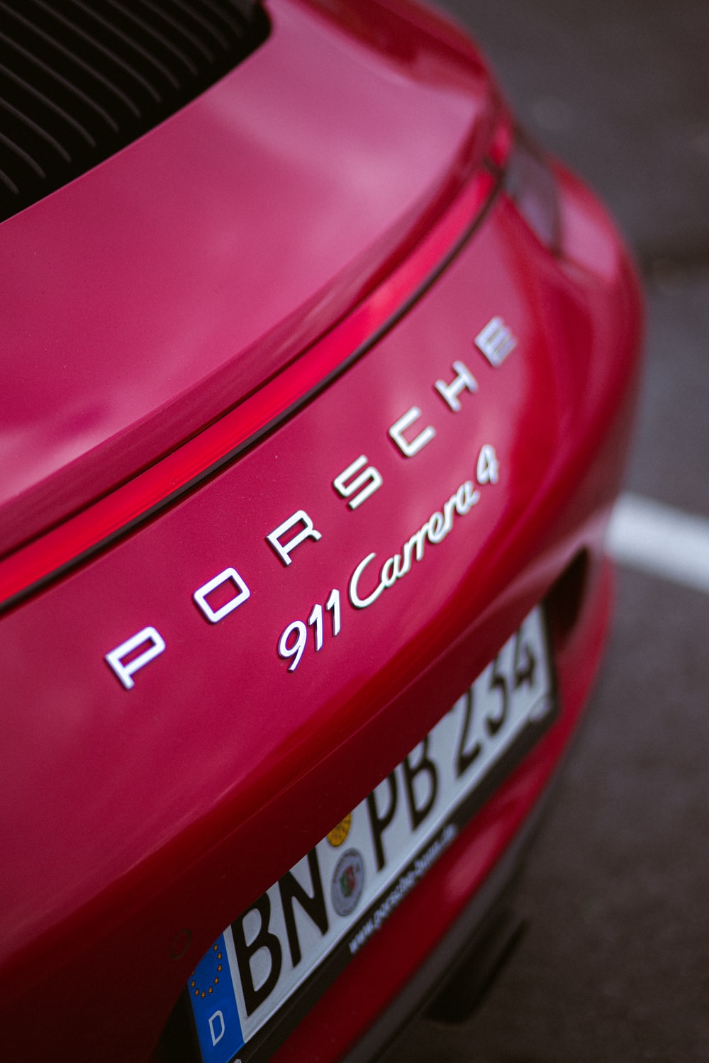 shallow focus photo of red Porsche 911 Carrera 4