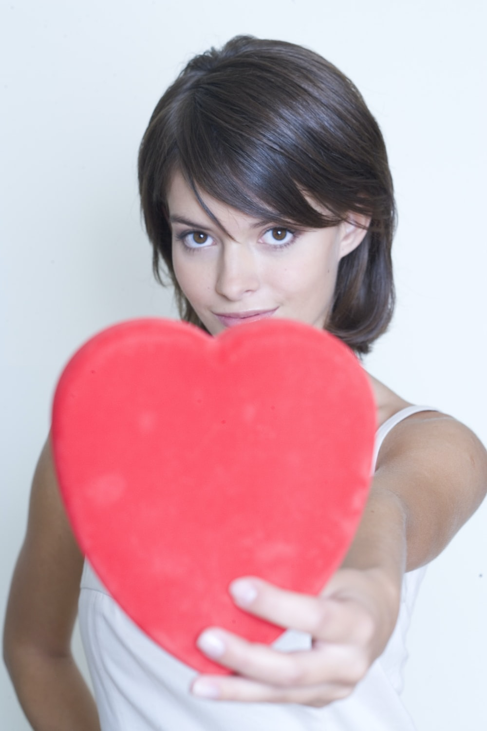 woman holding red heart pillow