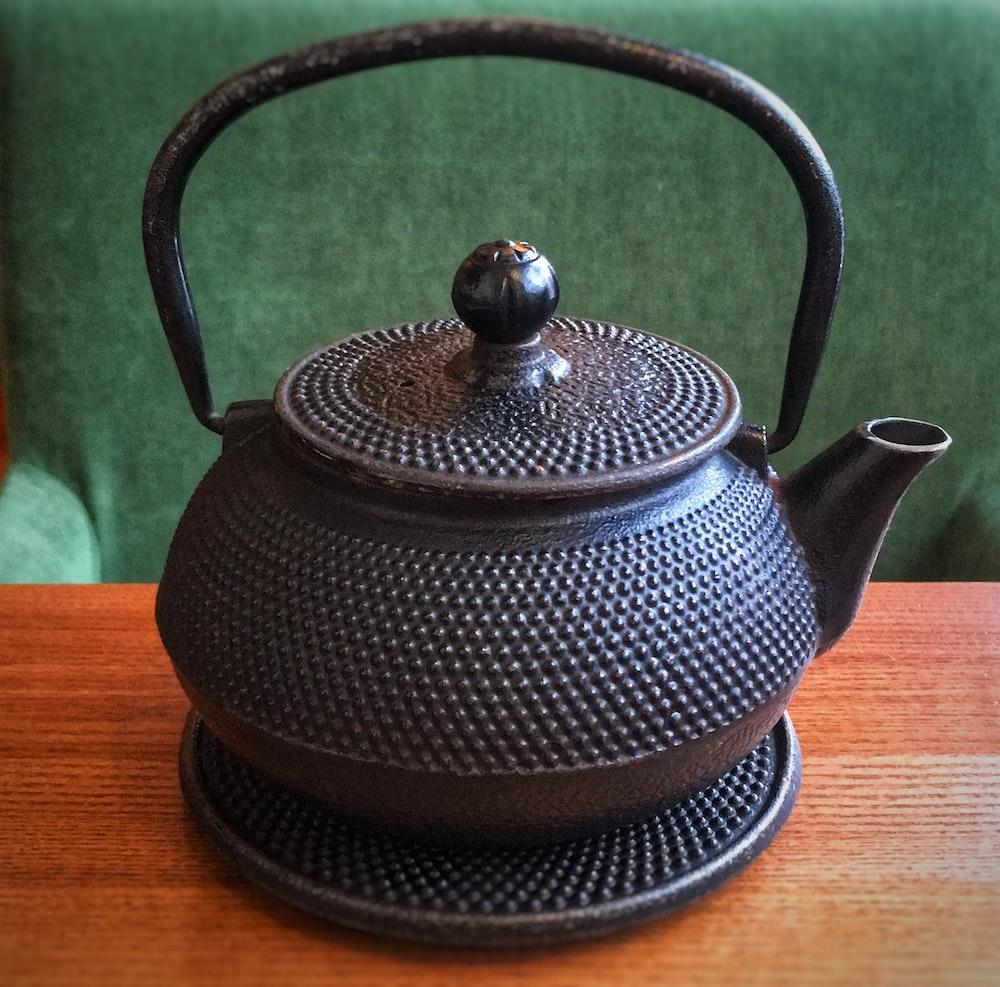 black teapot on wooden surface