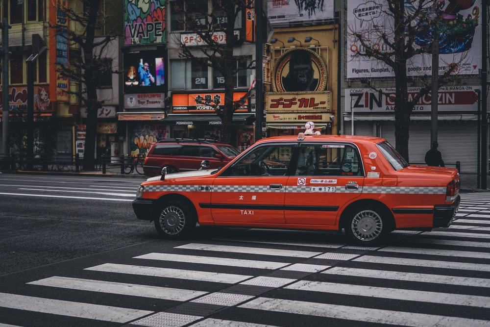 red taxi on pedestrian lane