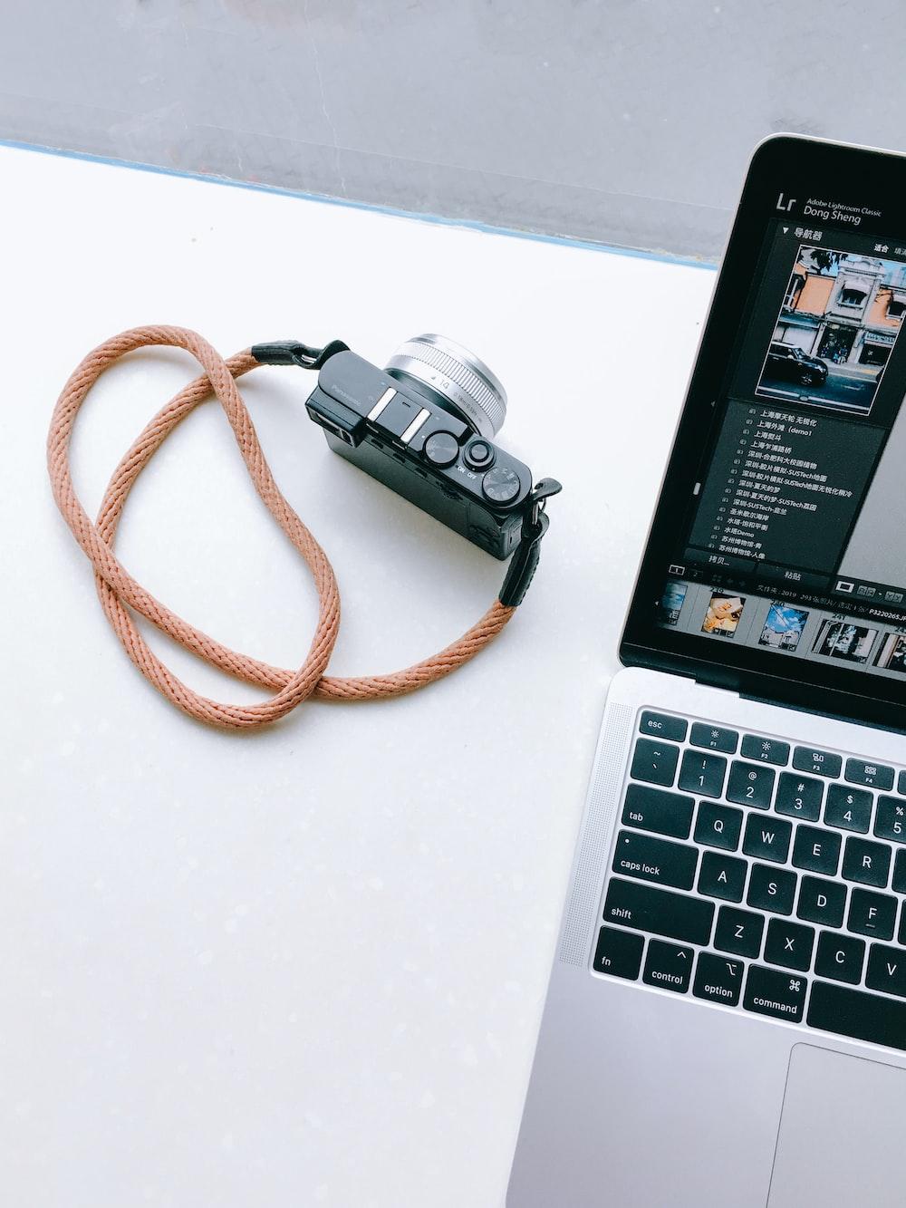 turned-on MacBook Pro near black and gray camera