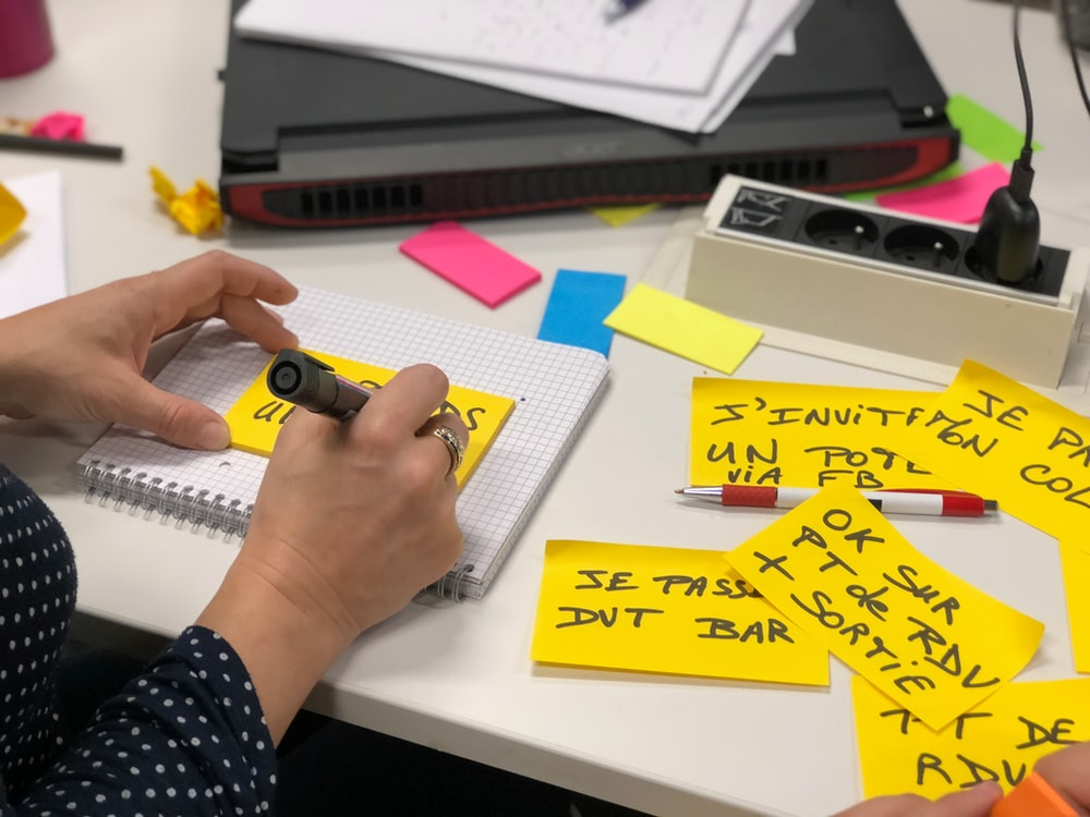 person writing on a sticky note using a marker