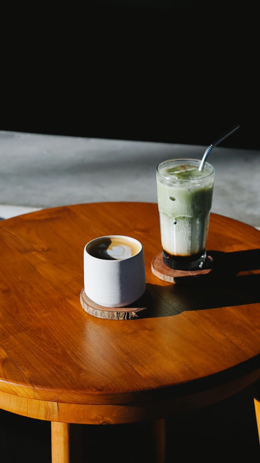 cup beside glass cup on table