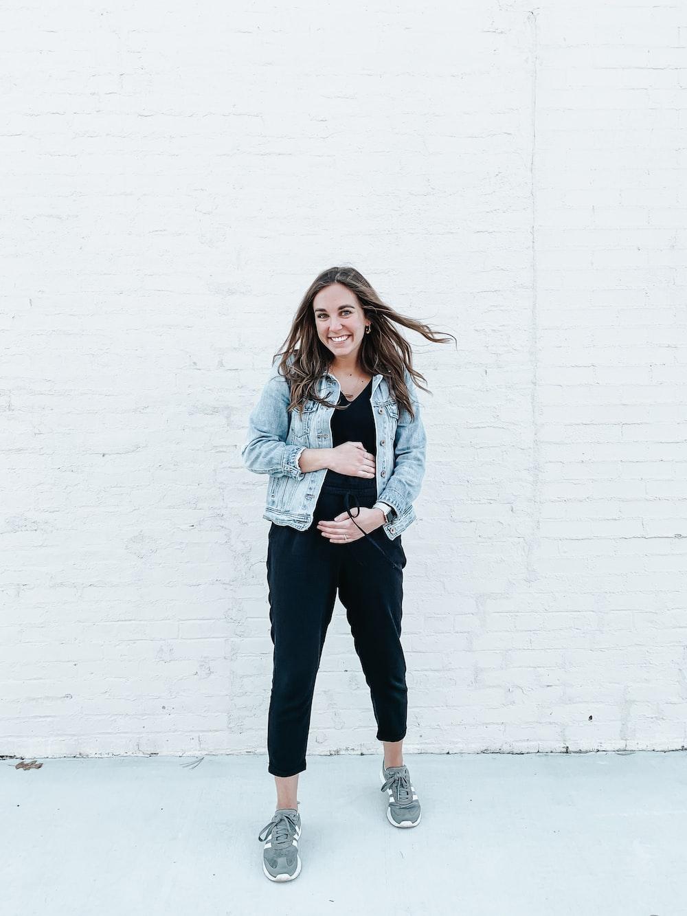woman in blue jeans standing beside wall