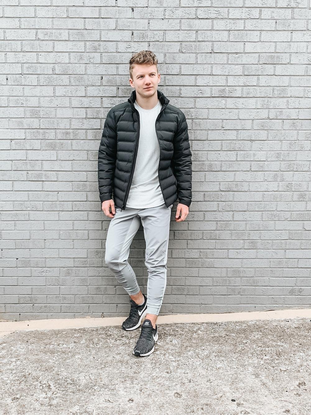 man in black jacket standing beside wall