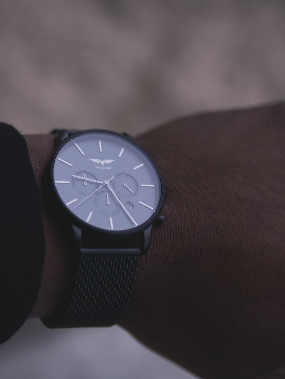 shallow focus photo of person wearing round black chronograph watch