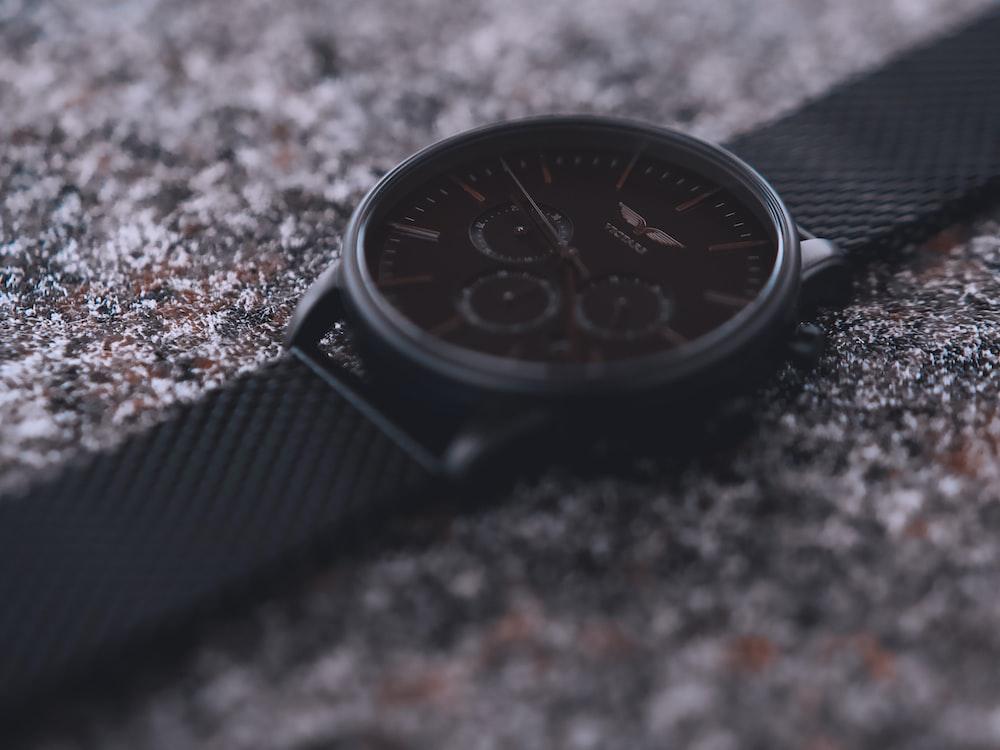 shallow focus photo of round black chronograph watch