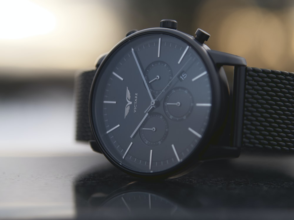 shallow focus photo of round black chronograph watch