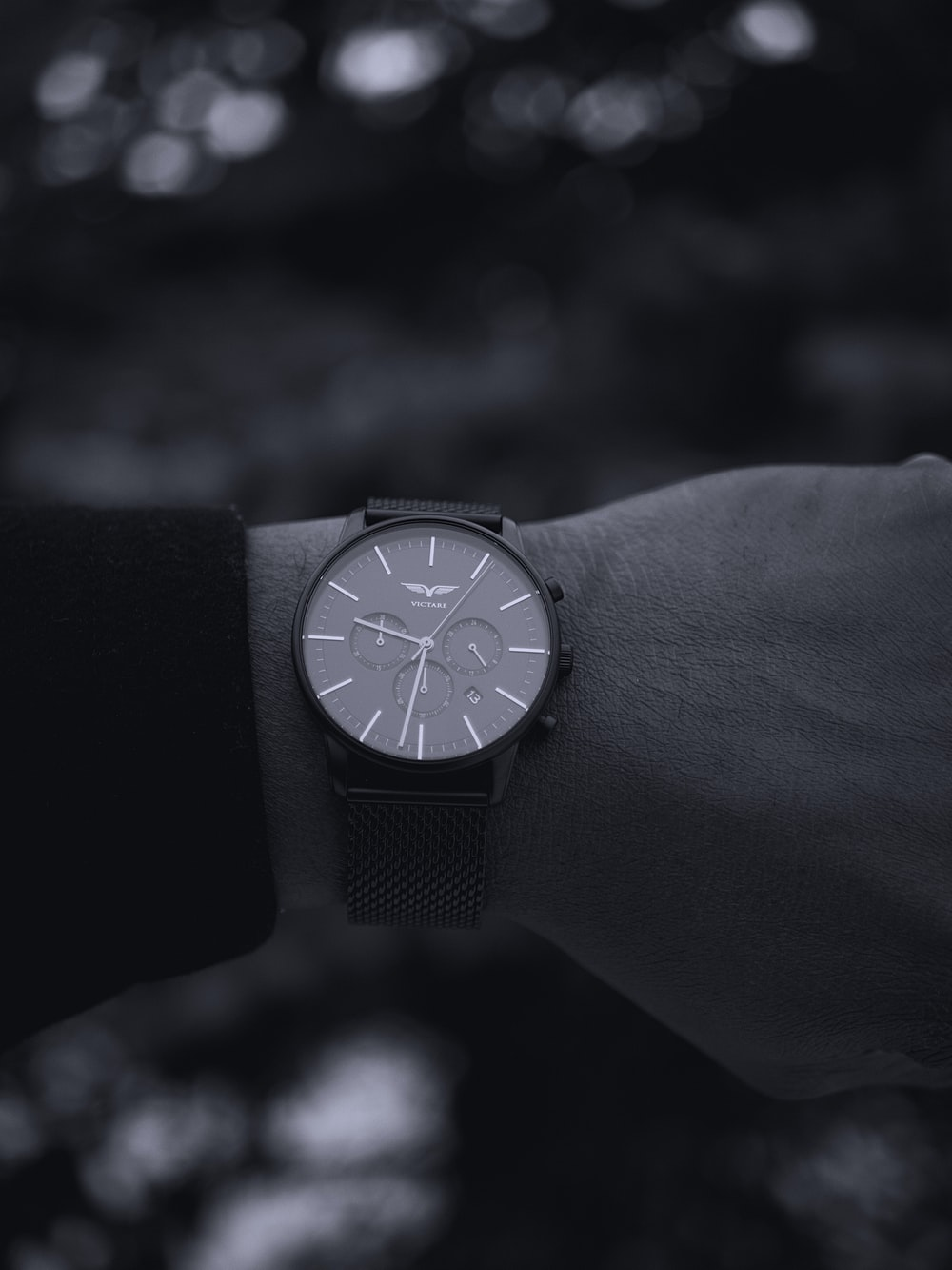 grayscale photo of person wearing round black chronograph watch