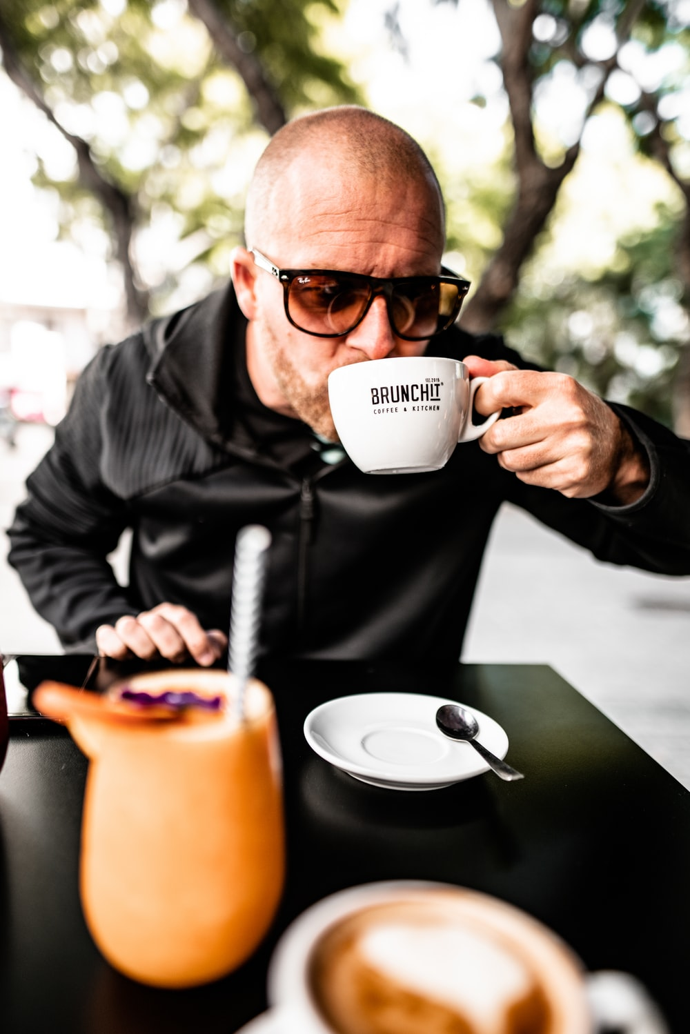 shallow focus photo of man drinking on white ceramic mug
