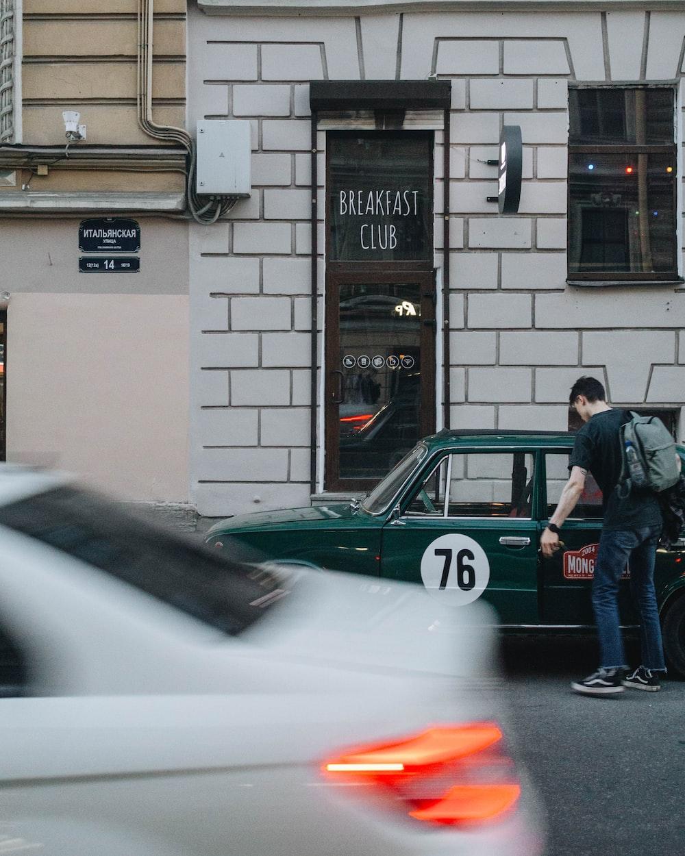 man opening door of green sedan