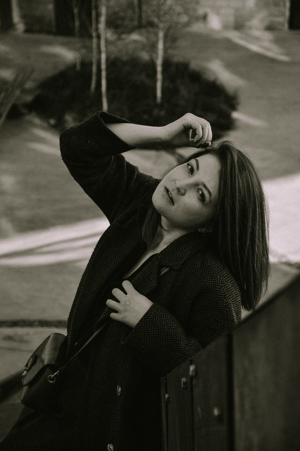 greyscale photo of woman leaning on fence