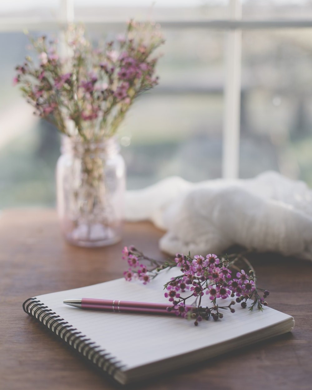 shallow focus photo of purple flowers on white spiral notebook