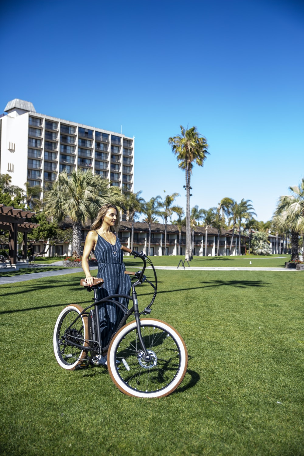 woman standing near bicycle on grass field