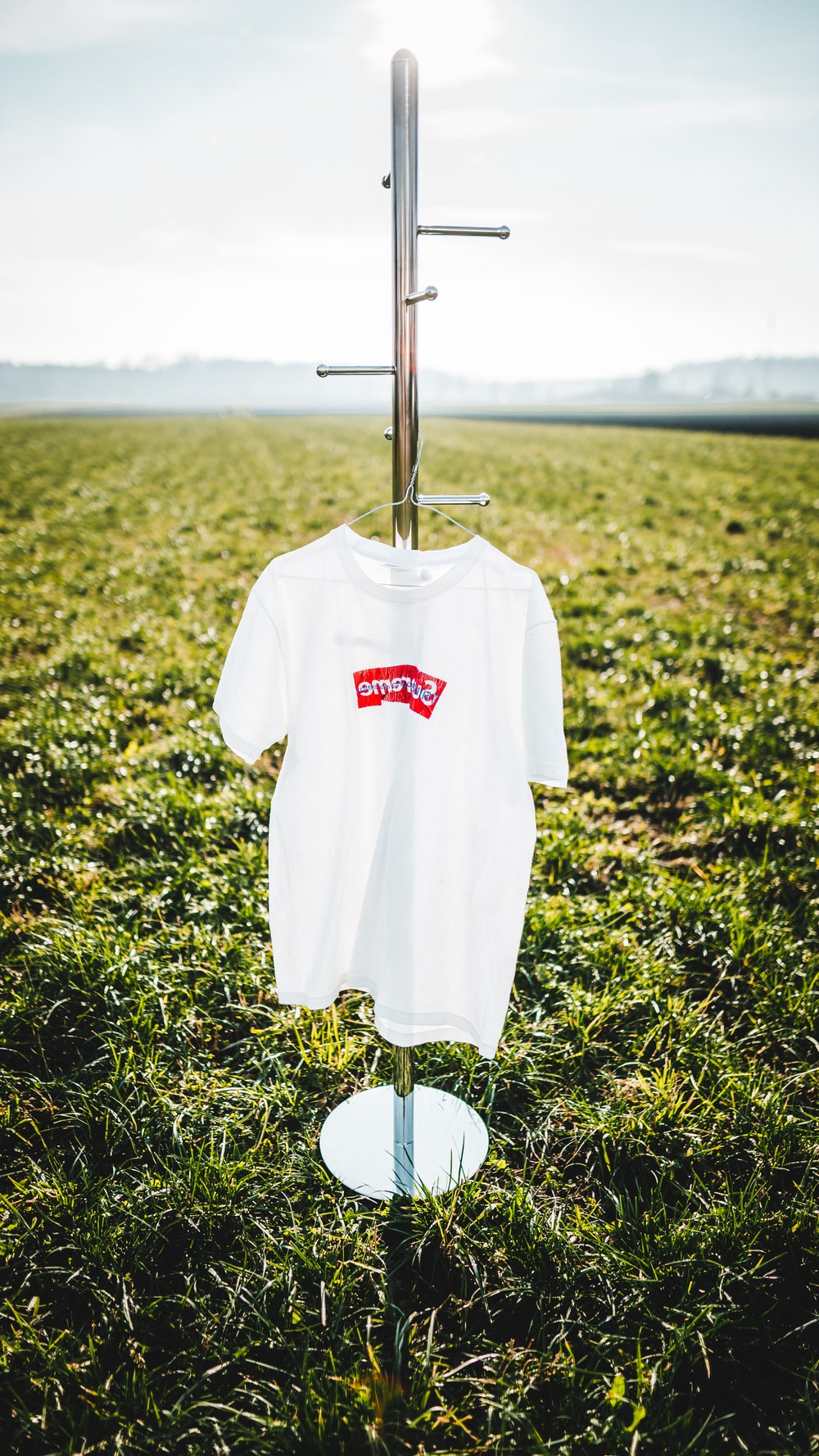 hanged white and red crew-neck shirt on display rack on green grass