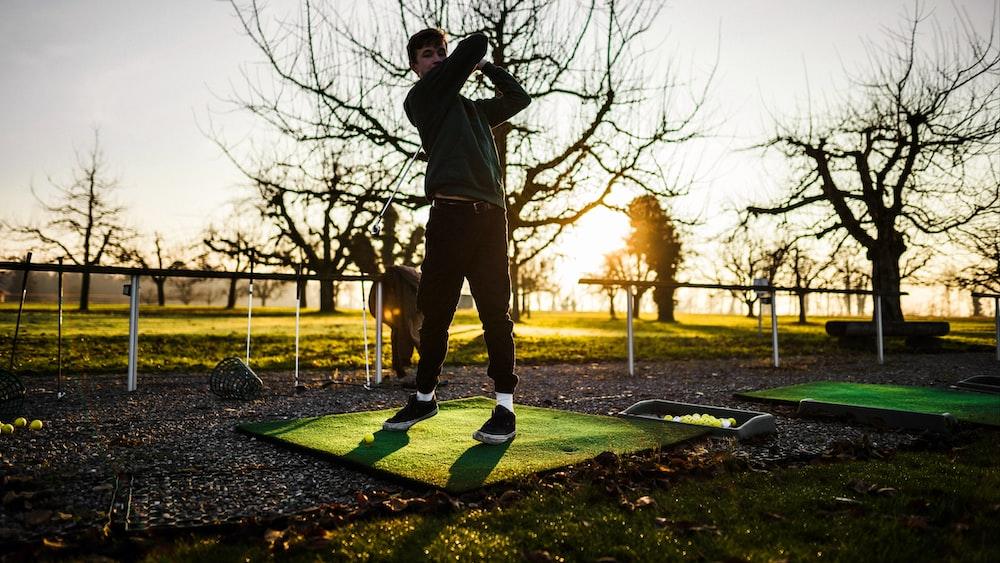 man plays golf at the farm