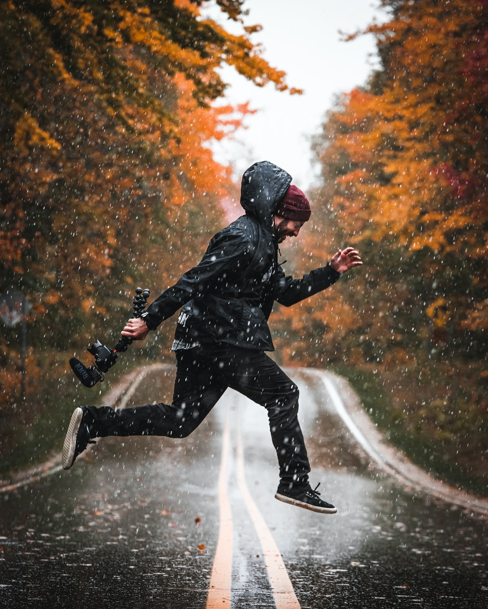 time-lapse photography of man jumping in a road while raining