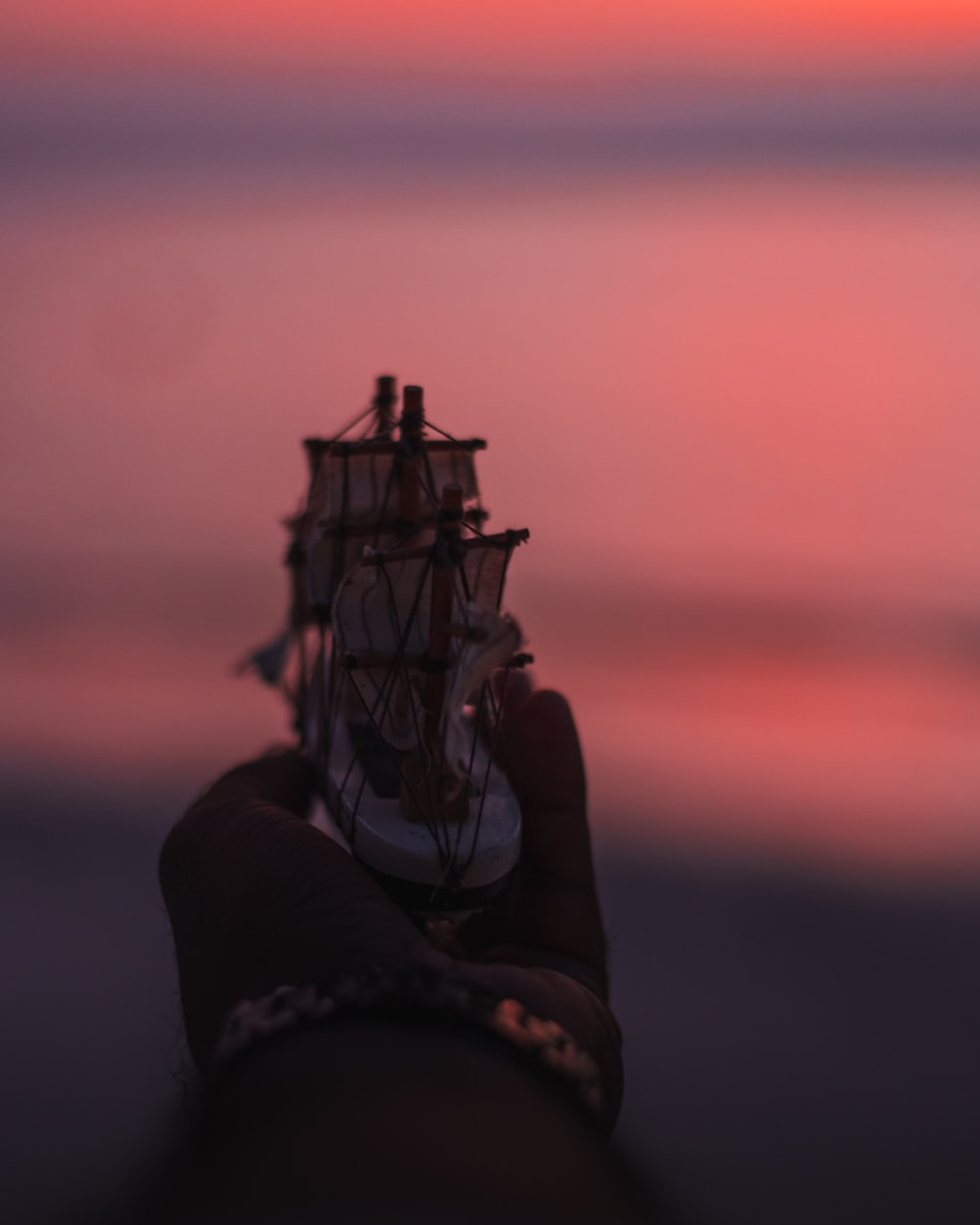 person holding a white and brown ship miniature