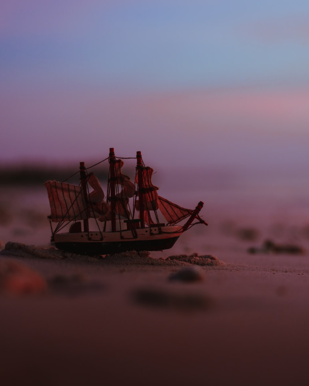 brown and white ship miniature by the seashore