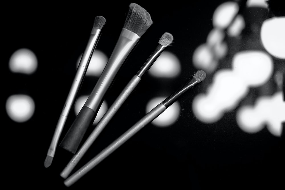 grayscale photo of makeup brushes