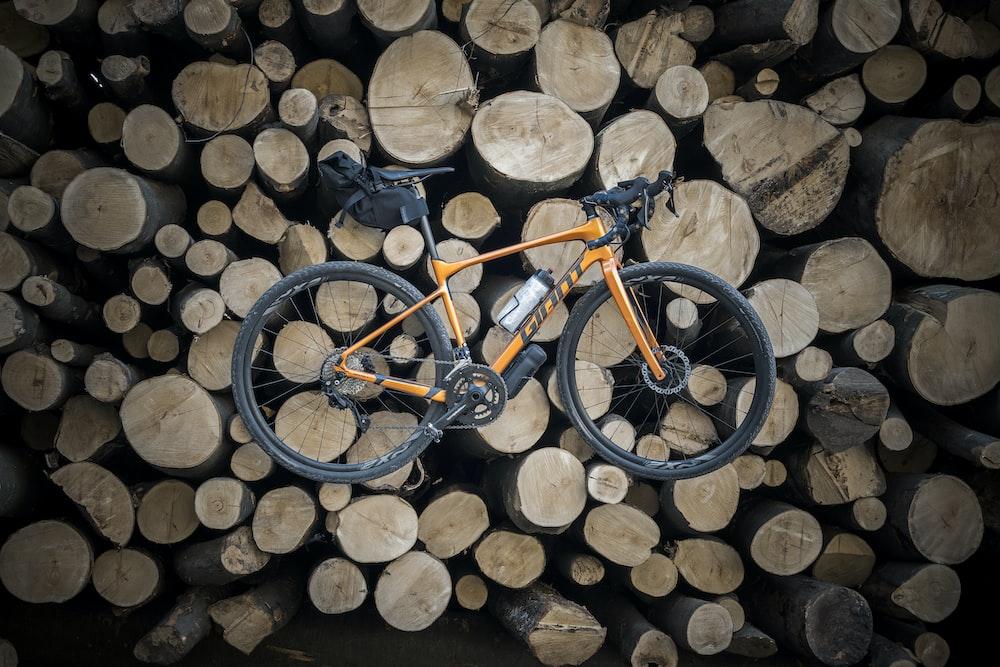 orange and black road bike on brown logs