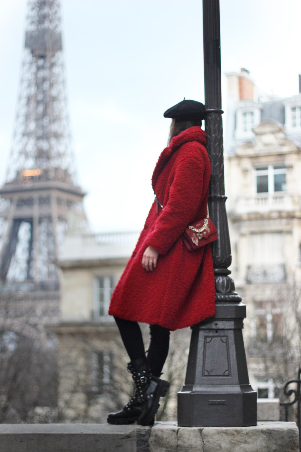 woman in red coat leaning on post lamp