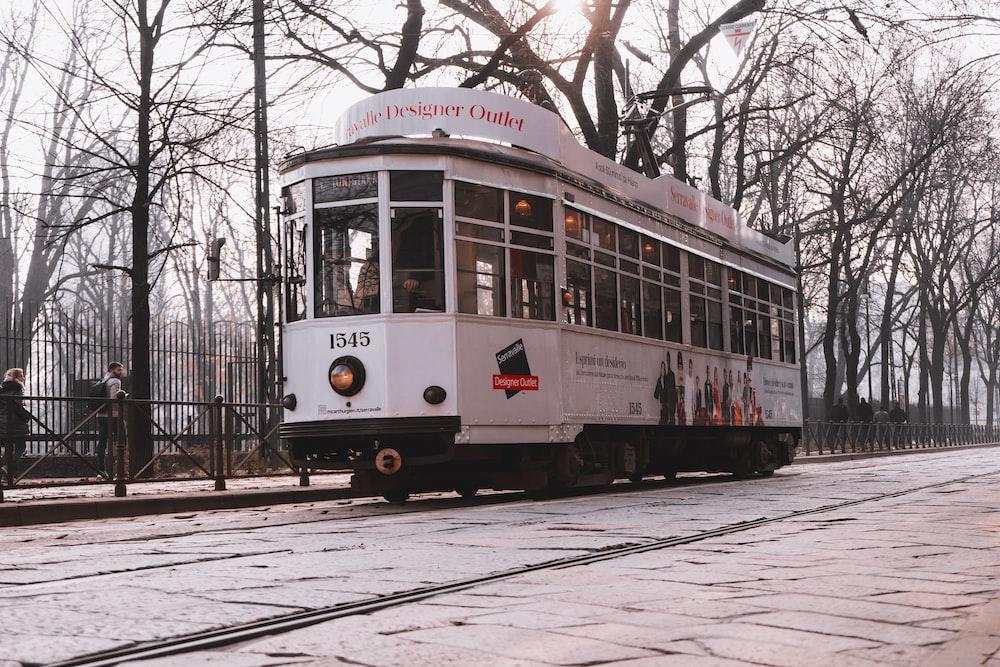 white tram crossing beside bare trees