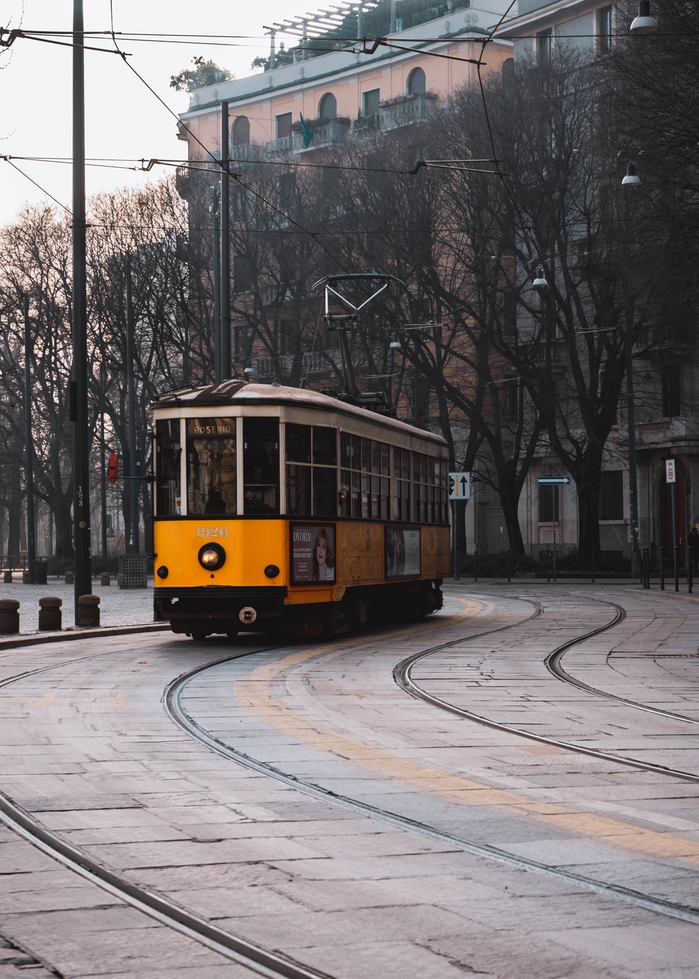 yellow tram crossing rail beside bare trees
