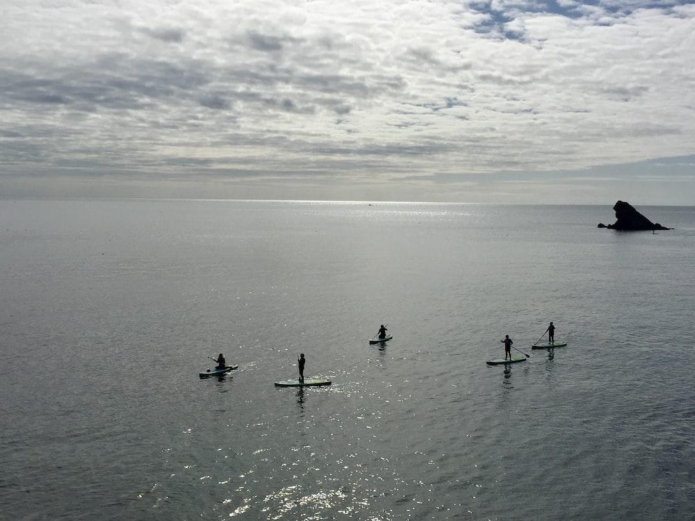 five people paddle boarding on sea