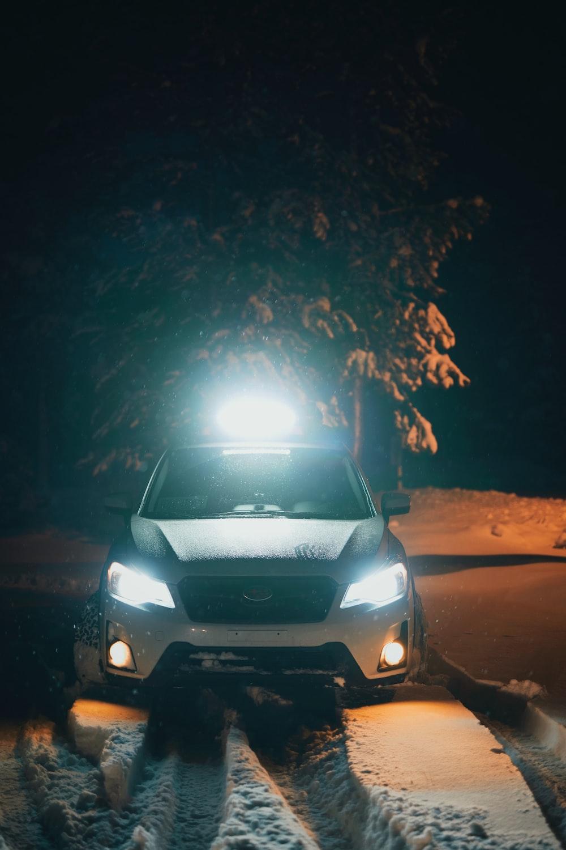 turned-on vehicle near tree