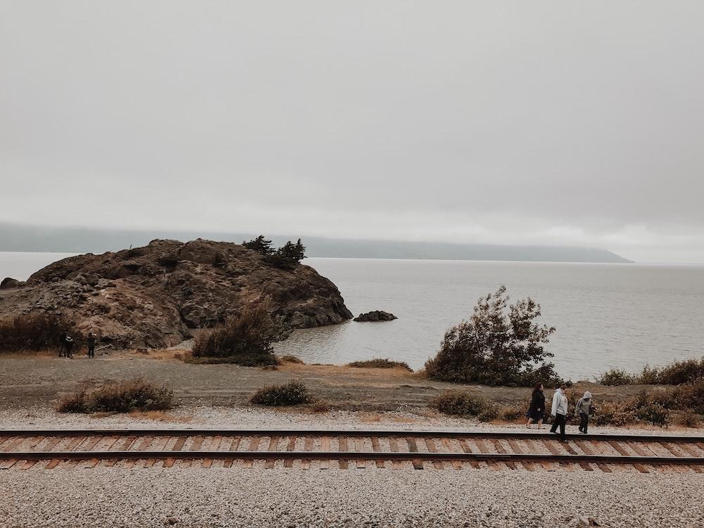 three person walking beside train rail
