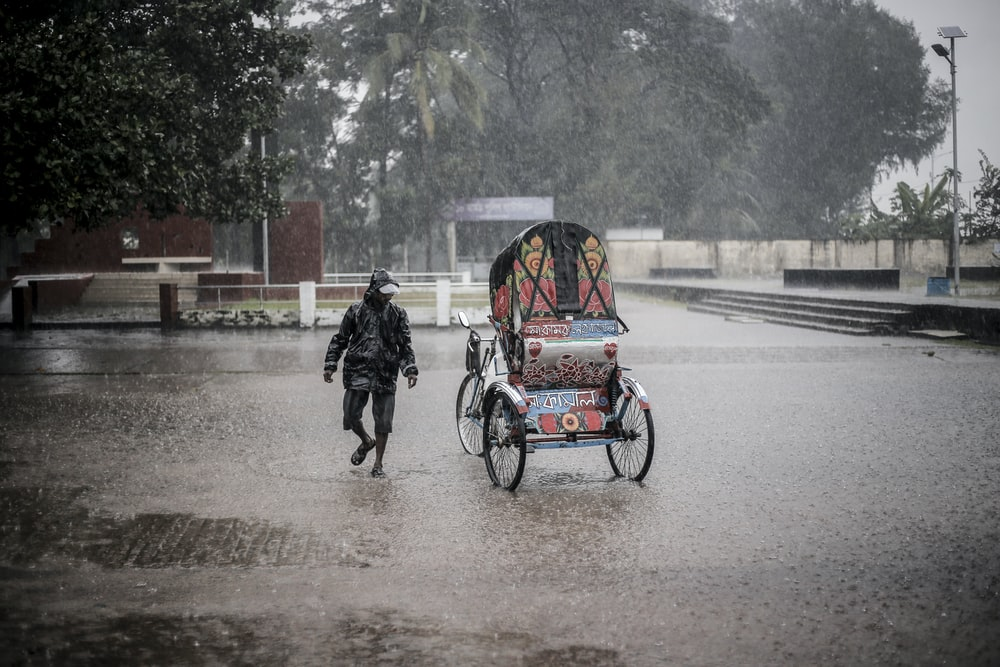 man walking beside trike during rain