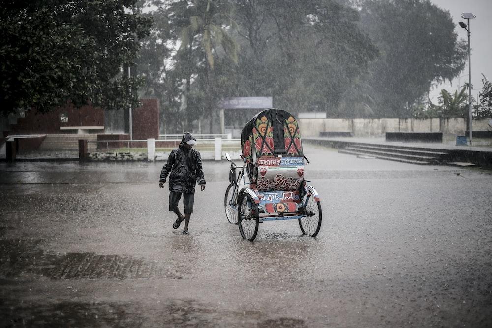man walking beside trike during rain