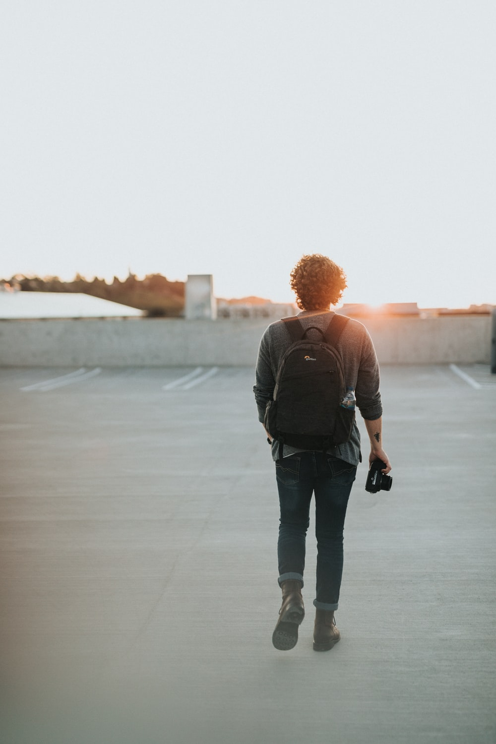 man wearing black backpack walking in front of the sun